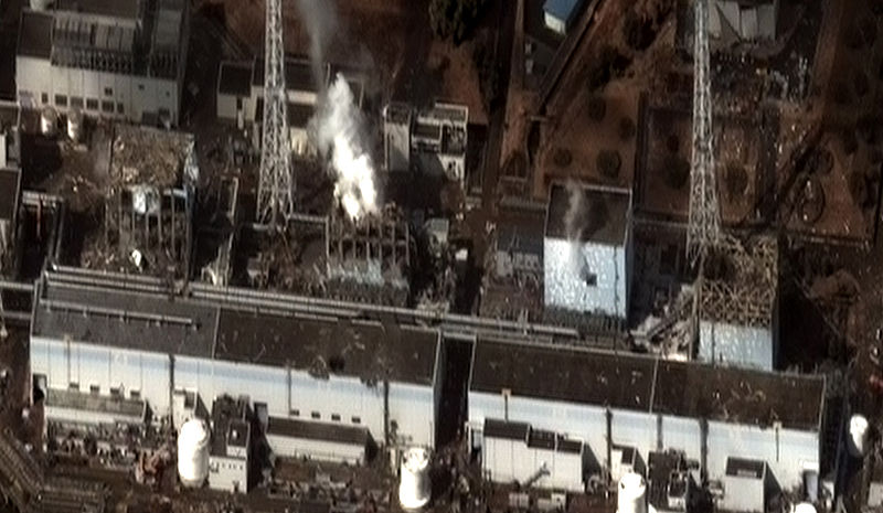 """Image on 16 March 2011 of the four damaged reactor buildings. From right to left: Unit 1,2,3,4. Hydrogen-air explosions occurred in Units 1,3,4 causing the building damage, while a vent in Unit 2's wall, with water vapor and """"steam"""" clearly visible, preventing a similar explosion."""