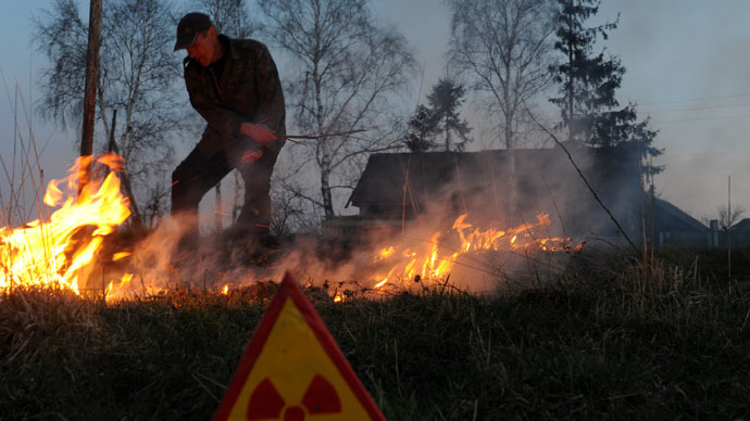 A man controls a fire as he burns his fallow field in the abandoned village of Rudnoye on April 20, 2011 close to the 30km exclusion zone around the Chernobyl nuclear reactor. (AFP Photo)