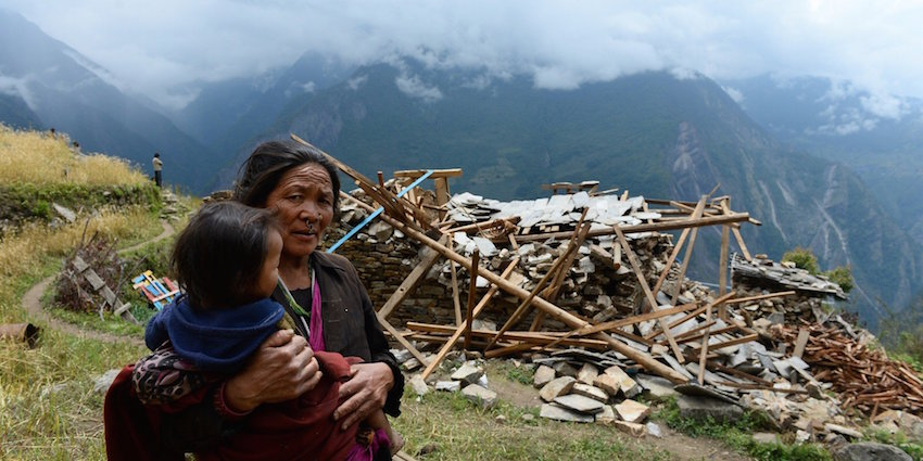 A mother carries her son as she walks past a damaged house at Uiya village, in northern-central Gorkha district on April 29, 2015. Hungry and desperate villagers rushed towards relief helicopters in remote areas of Nepal, begging to be airlifted to safety, four days after a monster earthquake killed more than 5,000 people. AFP PHOTO / SAJJAD HUSSAIN (Photo credit should read SAJJAD HUSSAIN/AFP/Getty Images)