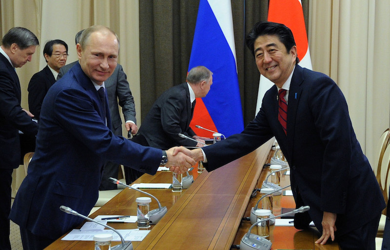 Russian President Vladimir Putin, left, and Japanese Prime Minister Shinzo Abe shake hands at their meeting in the Bocharov Ruchei residence in Sochi, Russia, Saturday, Feb. 8, 2014. (AP Photo/RIA-Novosti, Mikhail Klimentyev, Presidential Press Service)
