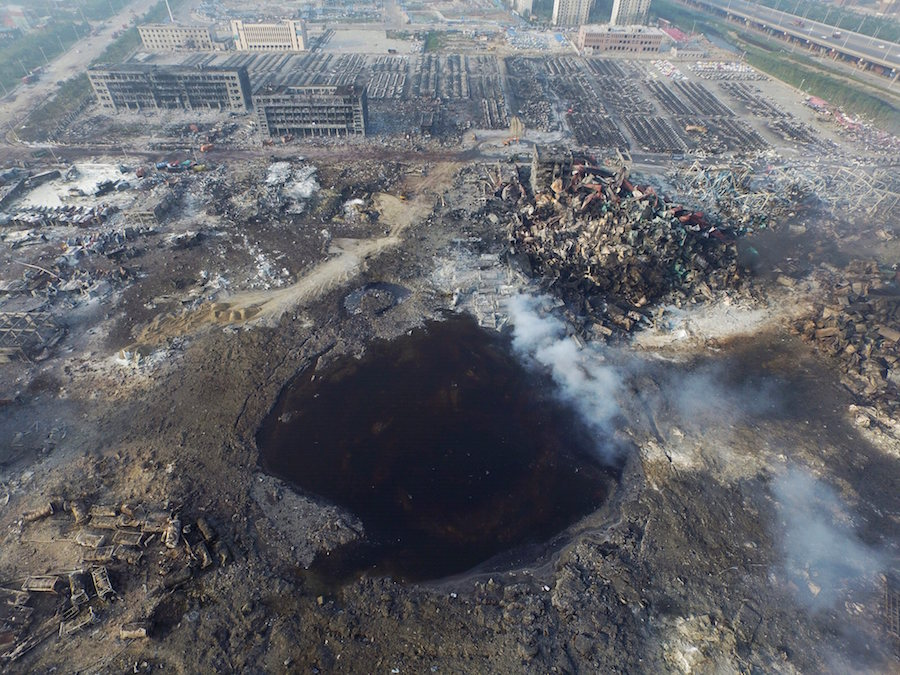 epaselect epa04884801 An aerial view of a large hole in the ground in the aftermath of a huge explosion that rocked the port city of Tianjin, China, 15 August 2015. Explosions and a fireball at a chemical warehouse killed at least 85 people in the north-eastern Chinese port city of Tianjin late on 12 August. New explosions rocked a chemical warehouse in northern China as police ordered residents to evacuate buildings within a three-kilometre radius, state media said on 15 August. EPA/STR CHINA OUT