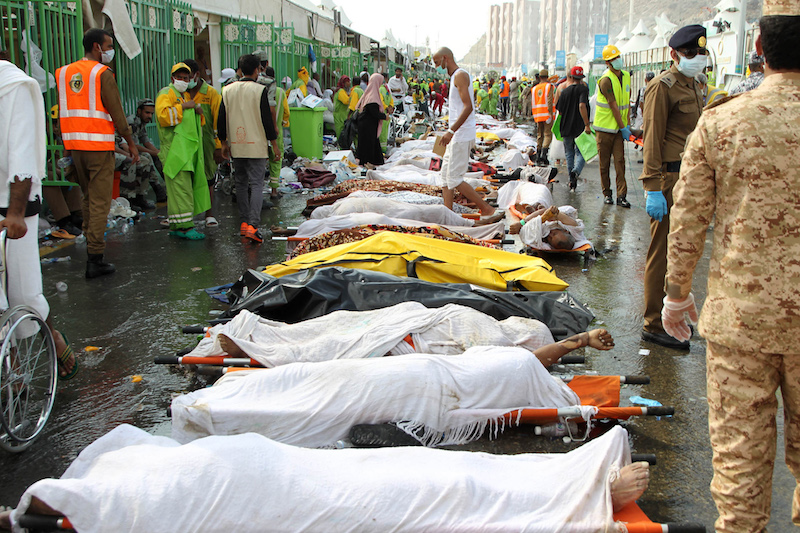 GRAPHIC CONTENT Saudi emergency personnel stand near bodies of Hajj pilgrims at the site where at least 717 were killed and hundreds wounded in a stampede in Mina, near the holy city of Mecca, at the annual hajj in Saudi Arabia on September 24, 2015. The stampede, the second deadly accident to strike the pilgrims this year, broke out during the symbolic stoning of the devil ritual, the Saudi civil defence service said. AFP PHOTO / STR