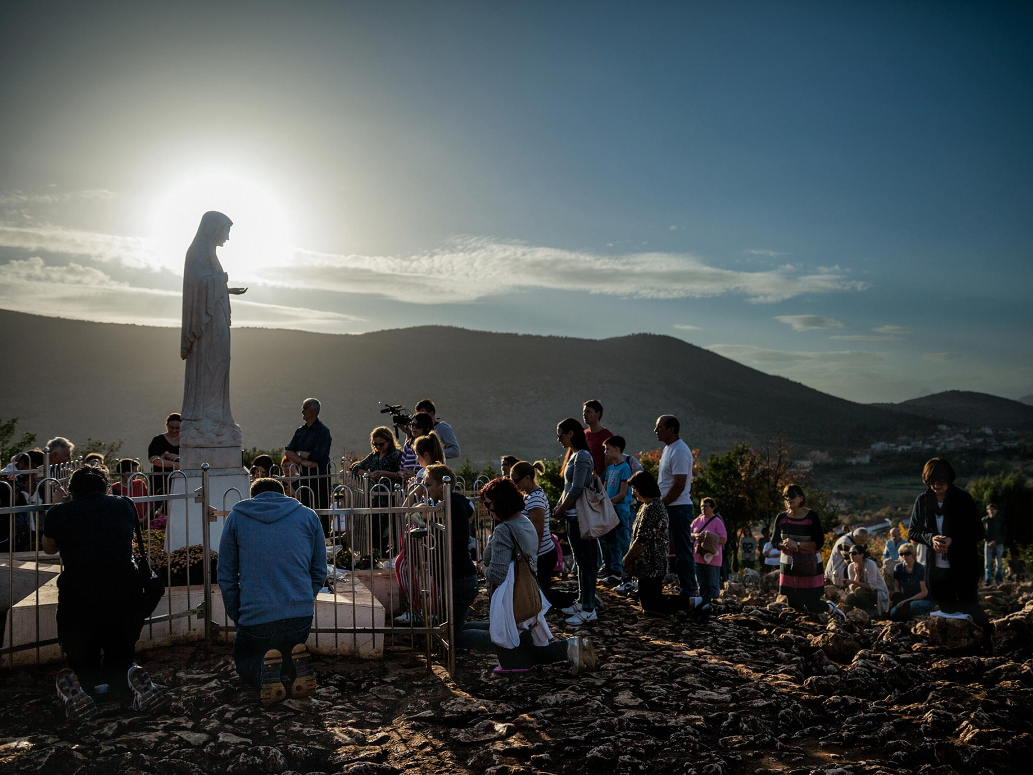 As the sun sets in Medjugorje, Bosnia and Herzegovina—a hot spot for Virgin Mary sightings—devotees of diverse faiths and nationalities gather to pray.
