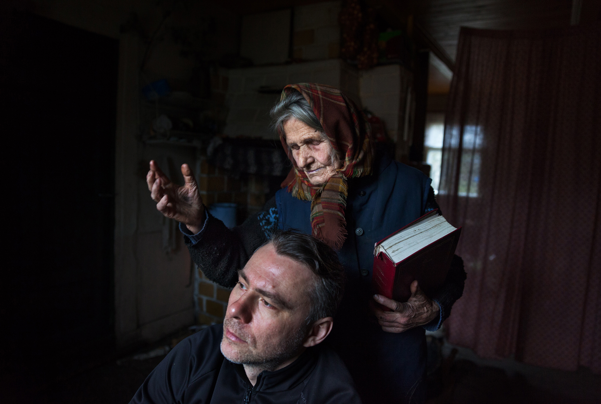 In Rutka, Poland, Anna Bondaruk, 84, prays with Marek Włodzimirow, 38, who has come to her for spiritual healing. Bondaruk says she has a direct connection to Mary that allows her to heal people.
