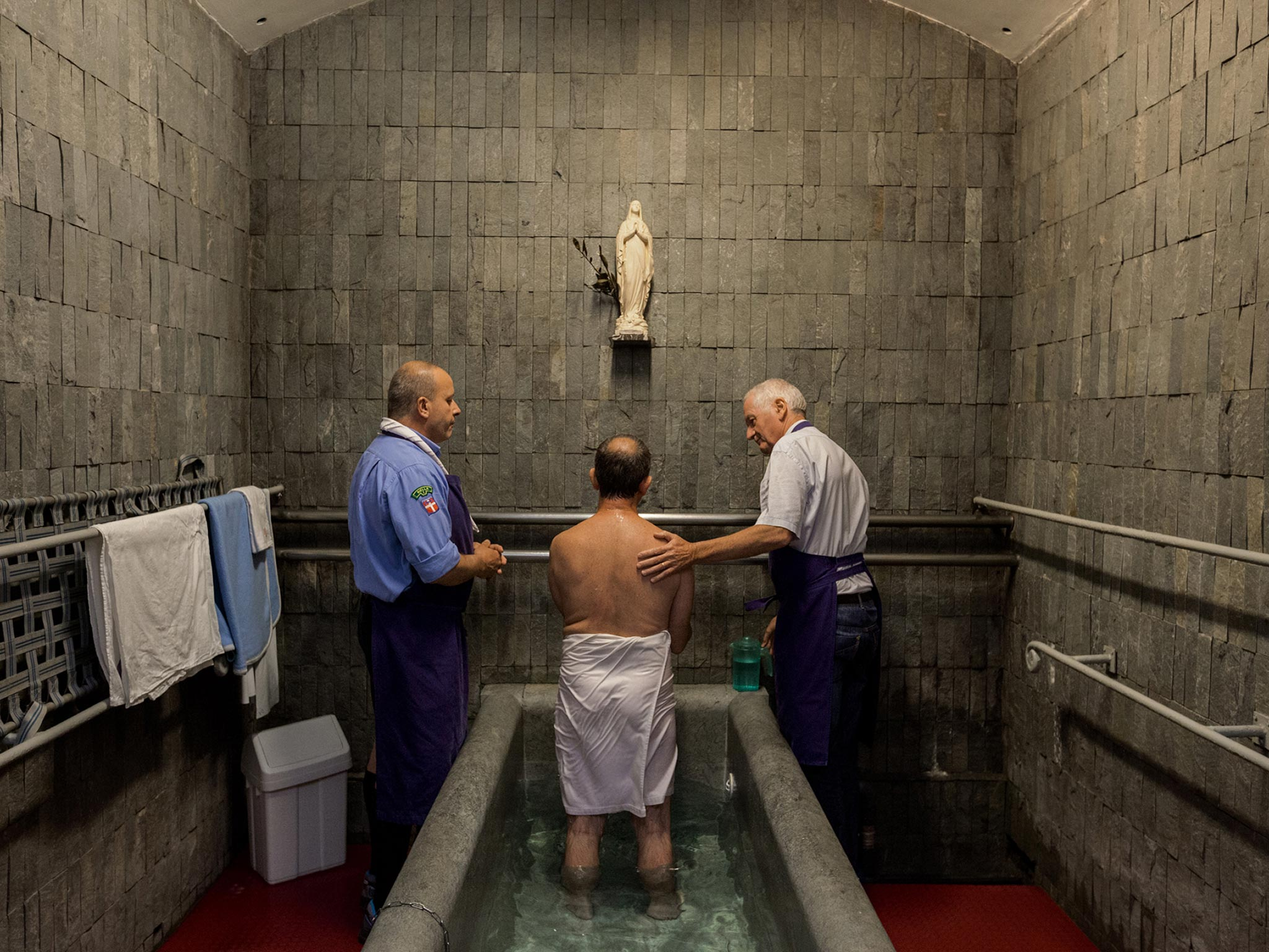 Volunteers help a man bathe in the ice-cold, spring-fed waters of Lourdes. The Massabielle Grotto has been the font of Lourdes's fame since 1858, when Mary is said to have appeared before a teenage girl and asked her to dig a spring in the hard earth. A small puddle soon grew into a pool; eventually it became this sacred water source, visited by some six million pilgrims every year.