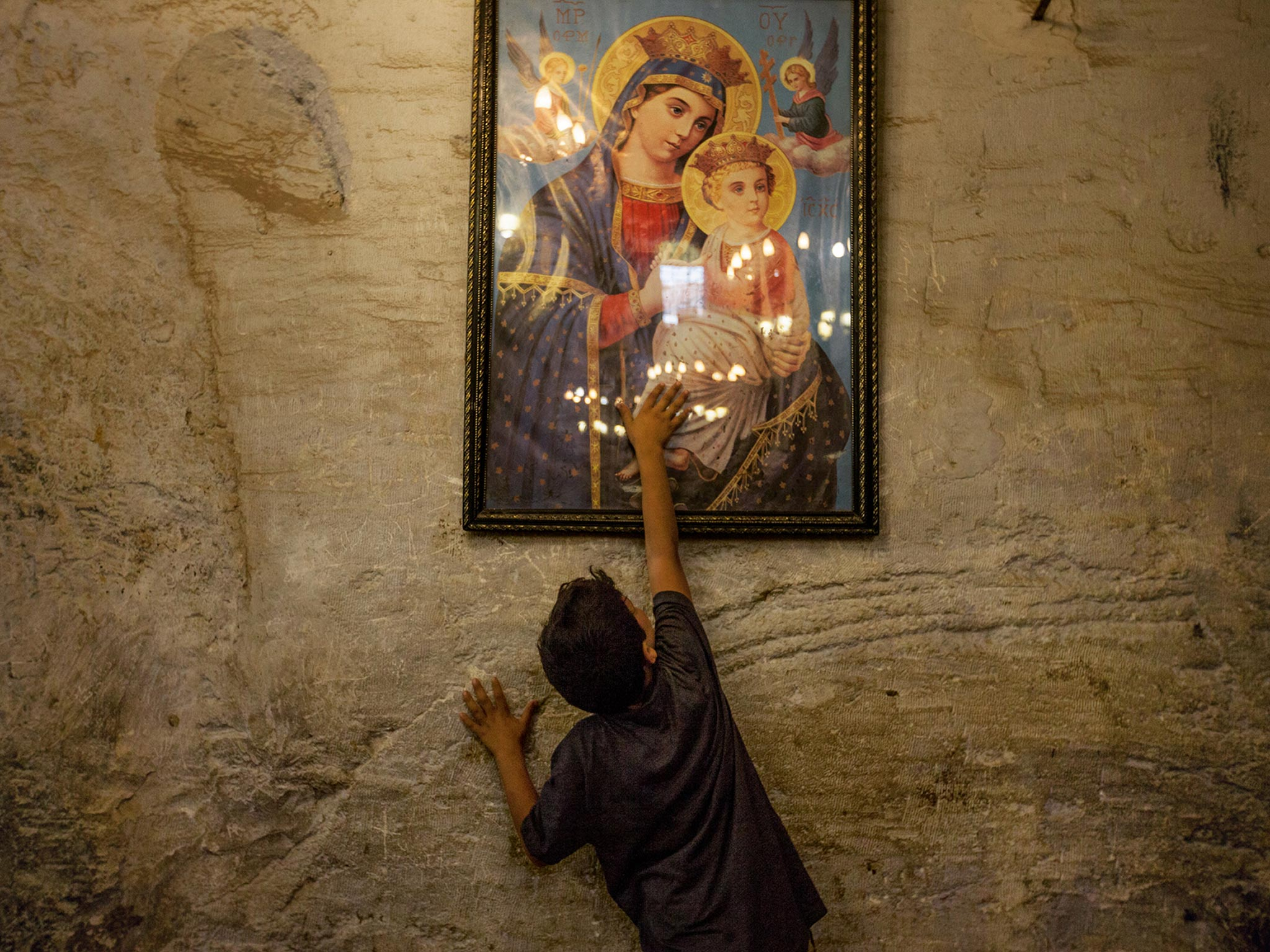 "A young boy in the Deir al Adra monastery reaches up to touch a painted image of Mary. In the Koran, Maryam (Mary) is the holiest woman mentioned. ""So the Virgin Mary is not at all strange to Muslims,"" says Roten. ""In fact, wherever there is a connection between Christians and Muslims—or any two groups that know and love her—there is a common value in the covenant mother."""