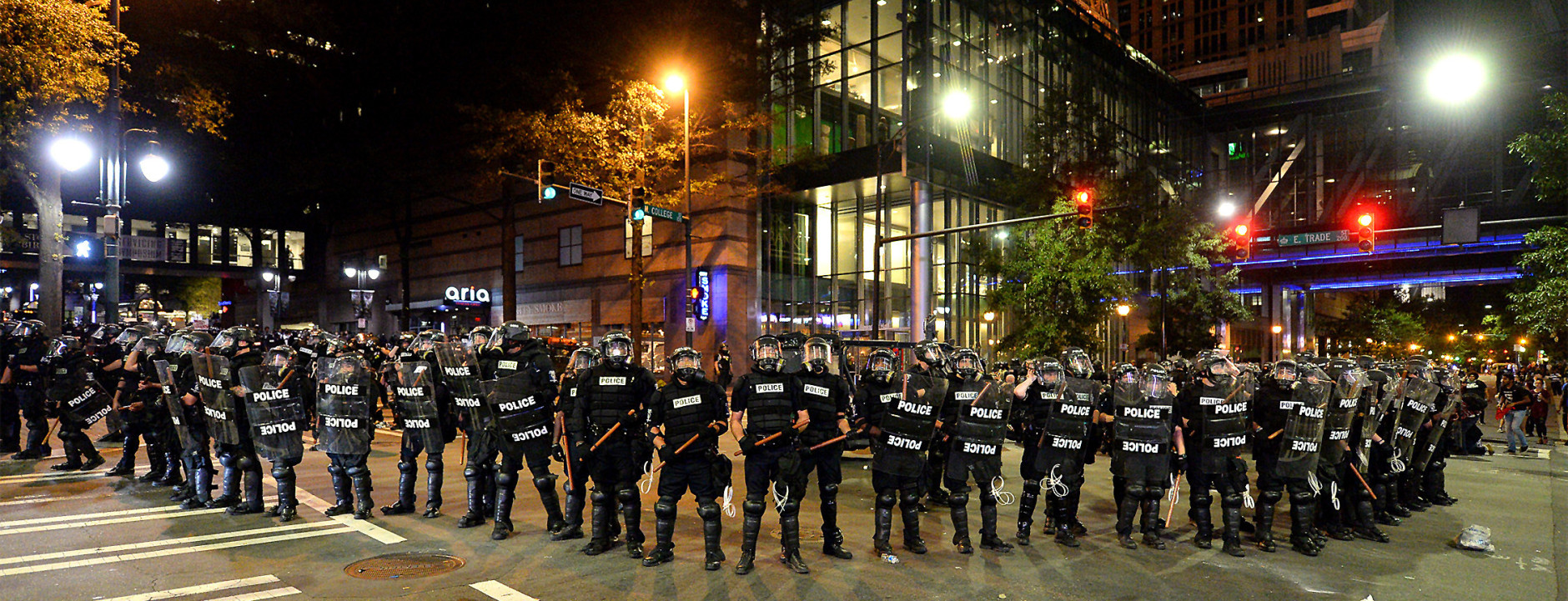 CMPD officers in riot gear block the intersection near the Epicentre in Charlotte, N.C. Wednesday, Sept. 21, 2016. Authorities in Charlotte tried to quell public anger Wednesday after a police officer shot a black man, but a dusk prayer vigil turned into a second night of violence, with police firing tear gas at angry protesters and a man being critically wounded by gunfire. North Carolina's governor declared a state of emergency in the city. (Jeff Siner/The Charlotte Observer via AP)