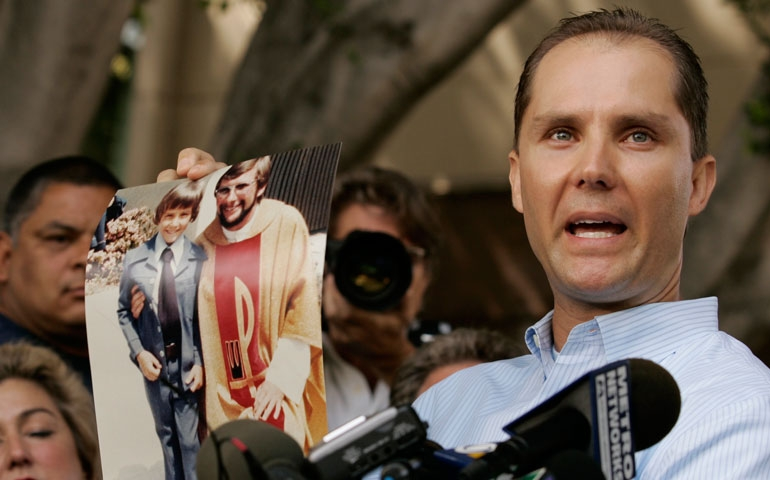 Plaintiff Lee Bashforth holds a photo of himself outside Los Angeles Superior Court on July 16, 2007, the day that the Los Angeles archdiocese and attorneys for more than 500 victims of clergy sex abuse arrived at a $660 million settlement. (AP Photo/Damian Dovarganes)