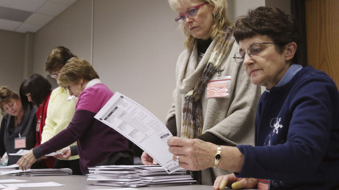 Tabulator Claudette Moll, right, from Farmington, looks over a ballot during a statewide presidential election recount Thursday, Dec. 1, 2016